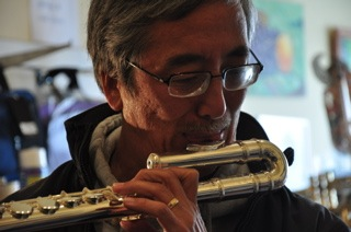 Bob Kenmotesu tries out a flute at Steve Deutsch Woodwinds