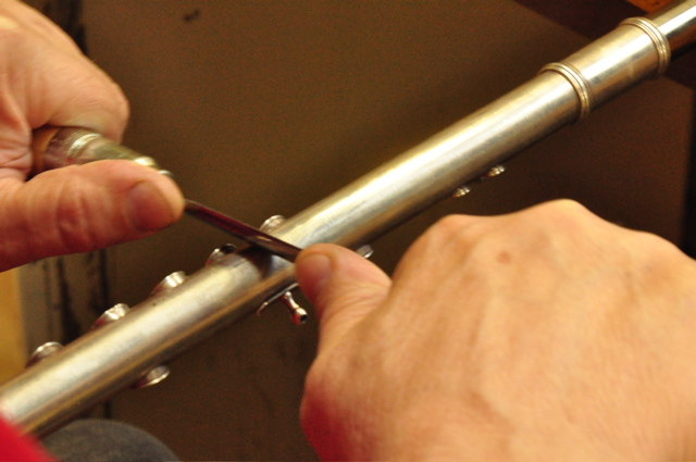 Removing dents and scratches from a flute at Vermont Flute Workshop.